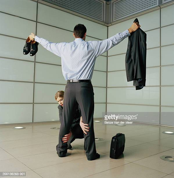 Woman frisking businessman, arms outstreched