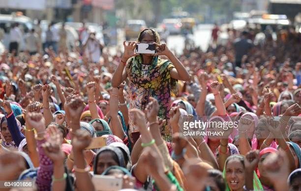 A woman from an Indian workers' union takes photos on a mobile phone during a protest in Ahmedabad on February 12 2017 Thousands of women working in...