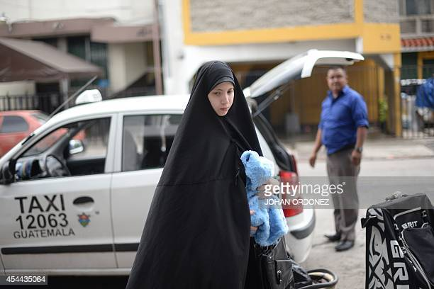 A woman from an ultraOrthodox Jewish group with her son in her arms arrives at the building where they will remain with their community in Guatemala...