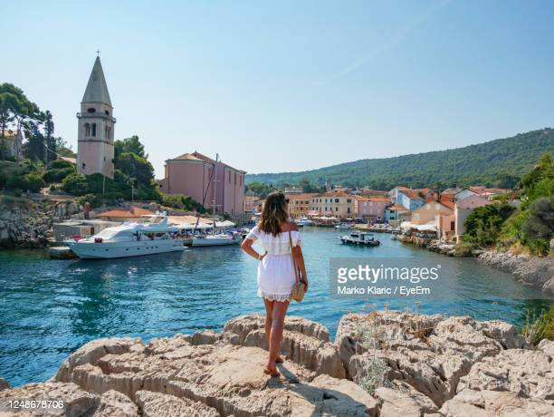 woman from behind, looking towards a picturesque old seaside town. - croatia stock pictures, royalty-free photos & images