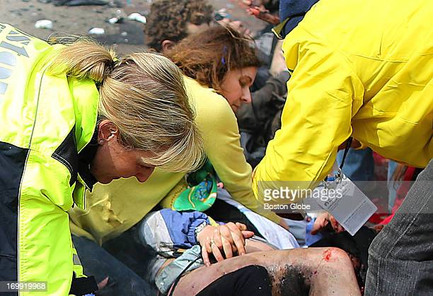 A woman from California helps Erika Brannock on the sidewalk at the site of the first explosion near the finish line of the Boston Marathon on April...