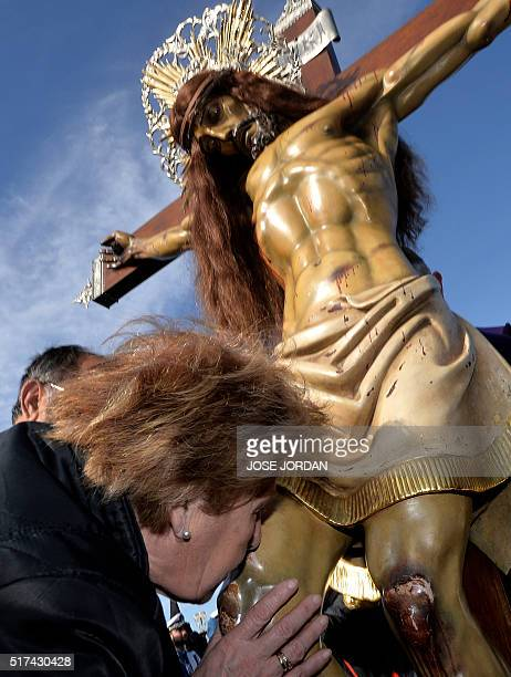 A woman from Cristo Salvador brotherhood kisses an effigy of Jesus Christ during a Holy Week procession on March 25 at the beach in Valencia...