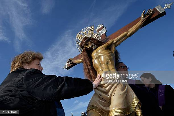 A woman from Cristo Salvador brotherhood touches an effigy of Jesus Christ during a Holy Week procession on March 25 at the beach in Valencia...