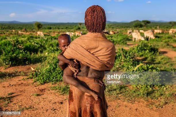frau aus dem stamm der hamer, die ihr baby in äthiopien trägt, afrika - afrikanischer volksstamm stock-fotos und bilder