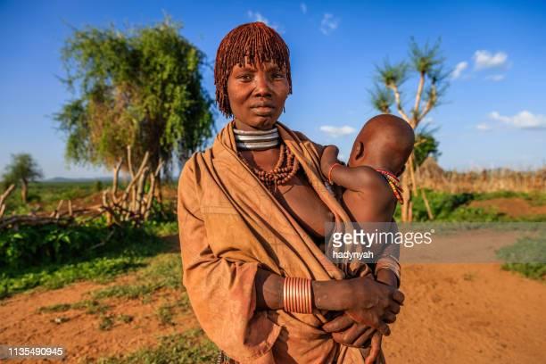 彼女の赤ちゃん、エチオピア、アフリカを運ぶハマー部族からの女性 - horn of africa ストックフォトと画像