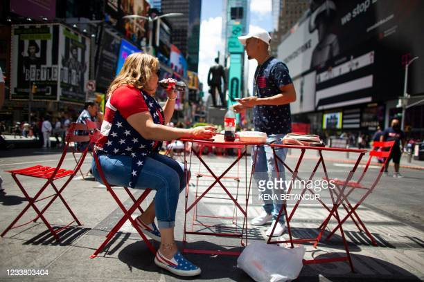 Woman from Honduras dresses with the American flag colors as she has a drink in Times Square during the US Independence Day holiday in New York on...