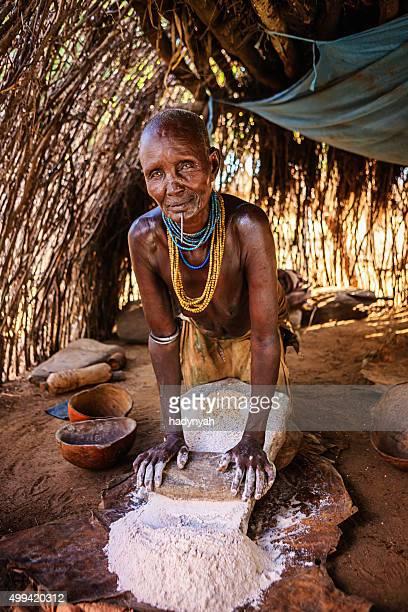 Woman from Karo tribe making sorghum flour, Ethiopia, Africa