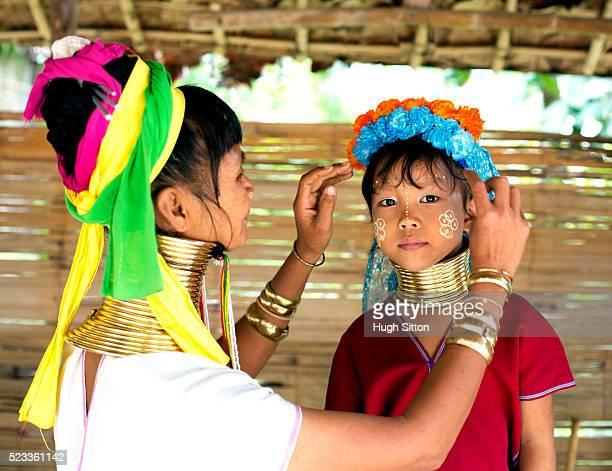 woman from long neck tribe putting wreath on girl's (6-7) head, chiang mai, thailand - hugh sitton bildbanksfoton och bilder