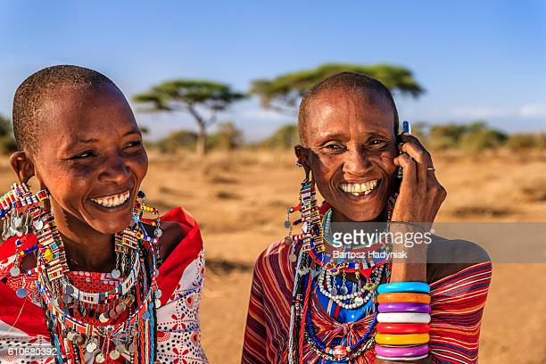 woman from maasai tribe using mobile phone, kenya, africa - indigenes volk stock-fotos und bilder