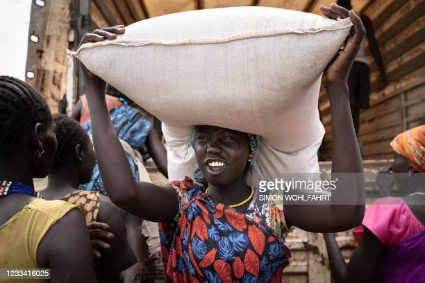 Woman from Murle ethnic group carries a bag of sorghum during a food distribution by United Nations World Food Programme in Gumuruk, South Sudan, on...