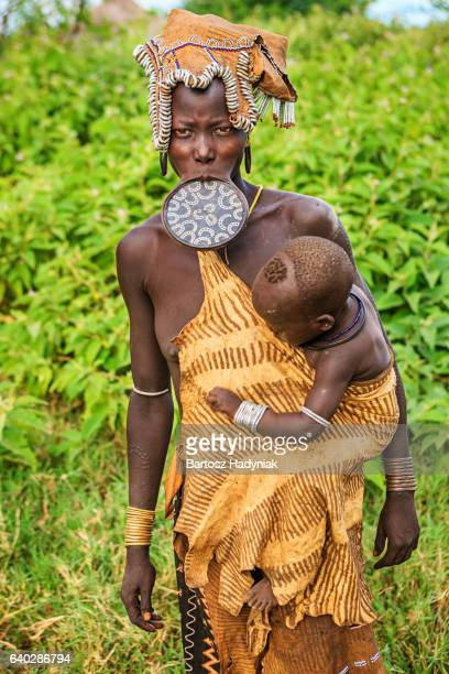 woman from mursi tribe breasfeeding her baby, ethiopia, africa - lip plate stock photos and pictures