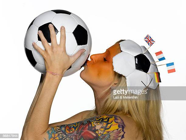 Woman from the Netherlands kissing soccer ball, eyes closed, side view