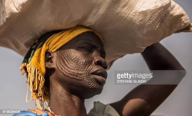 TOPSHOT A woman from Nuer ethnic group carries her food after a monthly food distribution at the Protection of Civilian site in Bentiu South Sudan on...