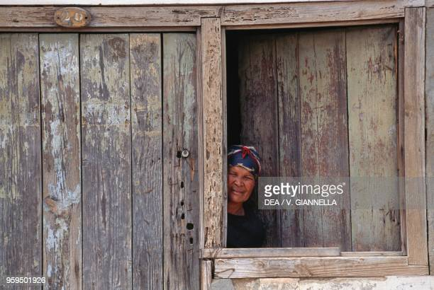 Woman from Pedra de Lume looking out the window, Sal Island, Cape Verde.