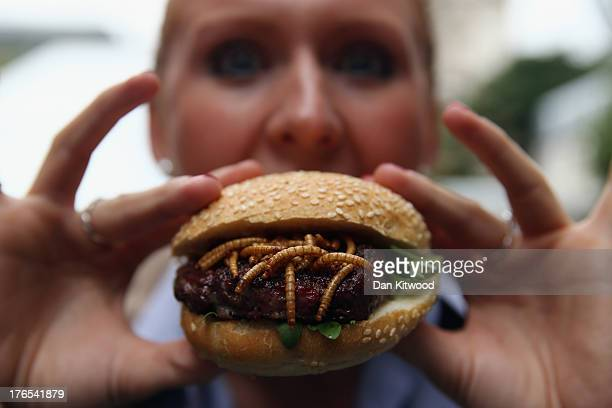 A woman from Rentokil poses with a Pigeon and Mealworm burger on a 'Pop Up' stand at One New Change on August 15 2013 in London England The pest...