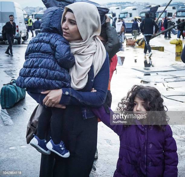 A woman from Syria holds her baby following they disembark at the port of Piraeus 29 September 2018 Thousand migrants and refugees are scheduled to...