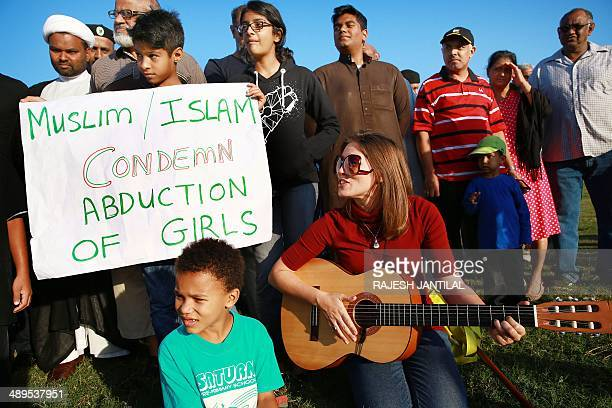 A woman from the Bahai Faith plays the guitar as she leads people from all faiths to pray for the immediate release of the abducted Nigerian school...