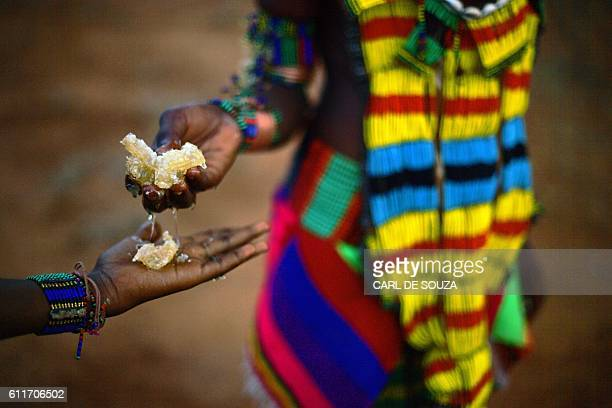 A woman from the Bena tribe shares honey collected from a tree in Ethiopia's southern Omo Valley region near Turmi on September 20 2016 The Bena are...