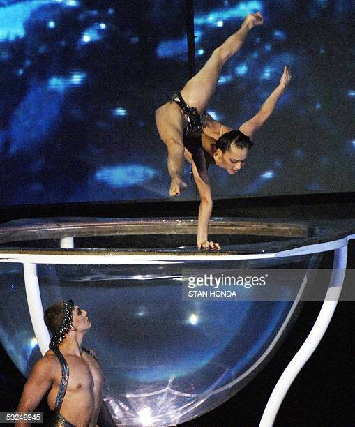 A woman from The Cirque du Soleil balances on a giant bowl as she performs at the opening ceremonies 16 July 2005 for the 2005 XI FINA World...