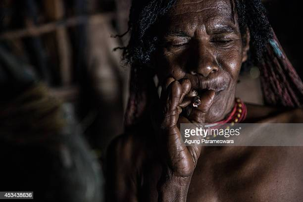 A woman from the Dani tribe with amputated fingers smokes a traditional cigarette at Obia Village on August 9 2014 in Wamena Papua Indonesia The Dani...