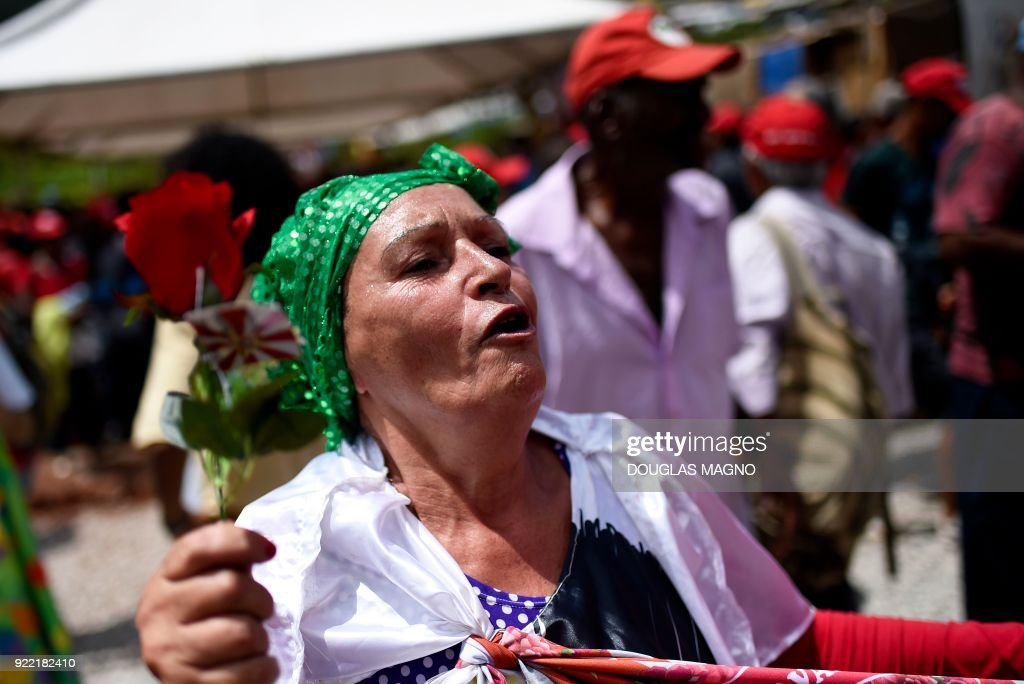 A woman from the Landless Workers Movement holds flowers to receive former president of Brazil, Luiz Inacio Lula da Silva, during a visit to their camp on the municipality of Itatiaiucu, Belo Horizonte in the state of Minas Gerais on February 21, 2018. Brazil's former leftist president Luiz Inacio Lula da Silva made yet another appeal against a 12 year prison sentence for corruption that could knock him out of an attempted comeback election. /