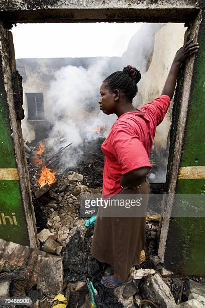A woman from the Luo tribe watches the smoldering remains of her shop after a group of members of the same tribe set fire to it after they acused...
