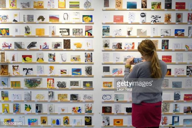 Woman from the Royal College of Art browses through the displayed postcards during a press preview ahead of the launch of the RCA Secret 2018...