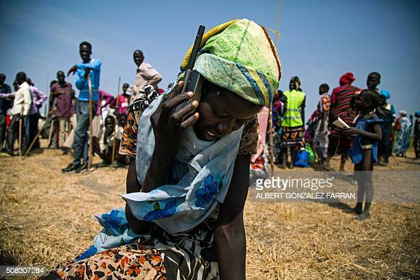 TOPSHOT A woman from Thonyor South Sudan uses a satellite phone provided by ICRC on February 3 2016 to call her lost relatives who fled the village...