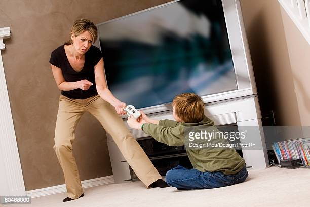 woman frustrated with boy for playing video game - stay at home mother stock-fotos und bilder
