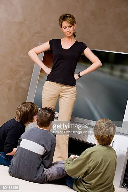 woman frustrated with boys for playing video game - stay at home mother stock-fotos und bilder