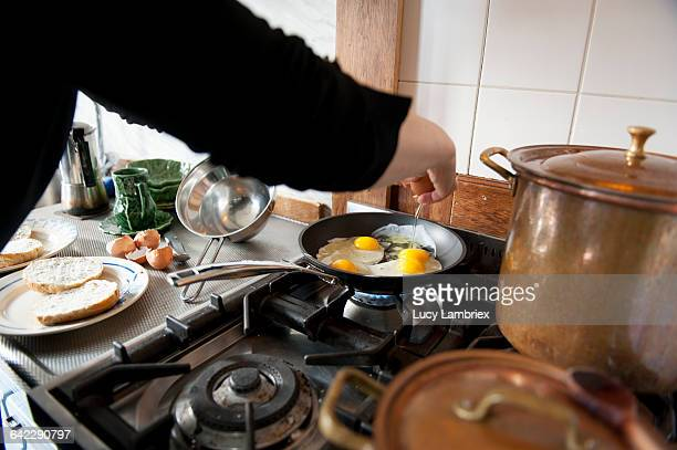 Woman frying eggs, sunny side up