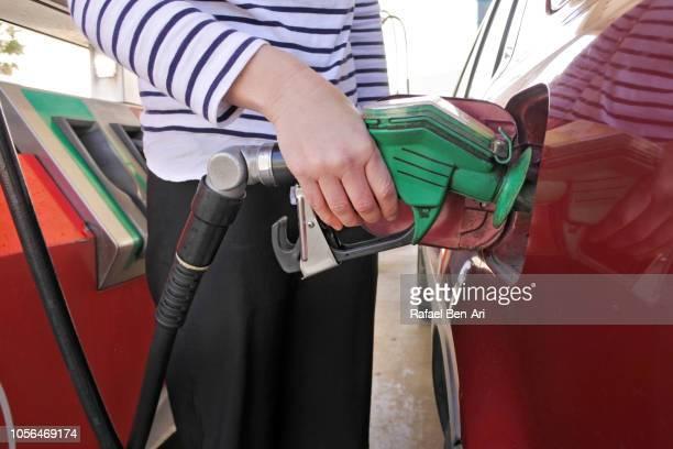 woman fulling a car in a gas station - rafael ben ari 個照片及圖片檔