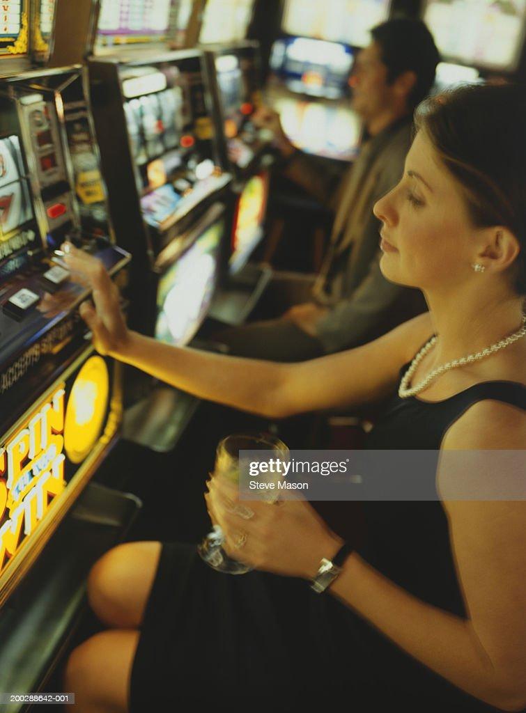 Woman gambling on slot machine in casino, side view : Stock Photo