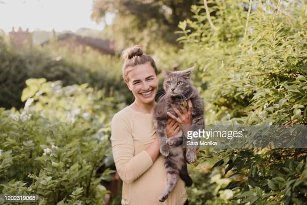 woman gardener carrying cat in garden - alleen één mid volwassen vrouw stockfoto's en -beelden