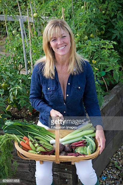 Woman gardener holding a trug and fresh vegetables