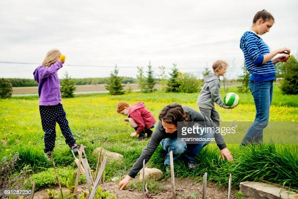 Woman gardening in home garden with children around.