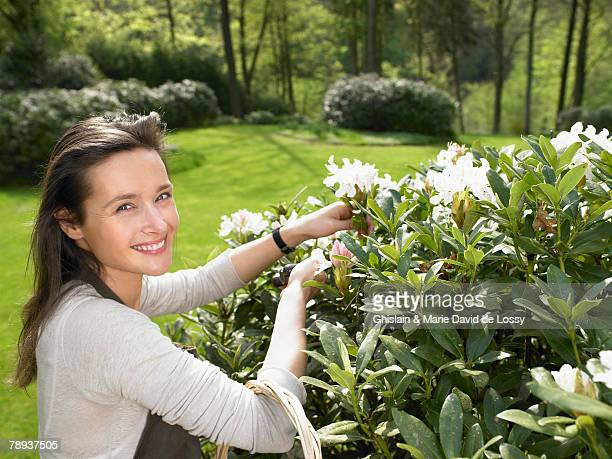 Woman gardening outdoors smiling.