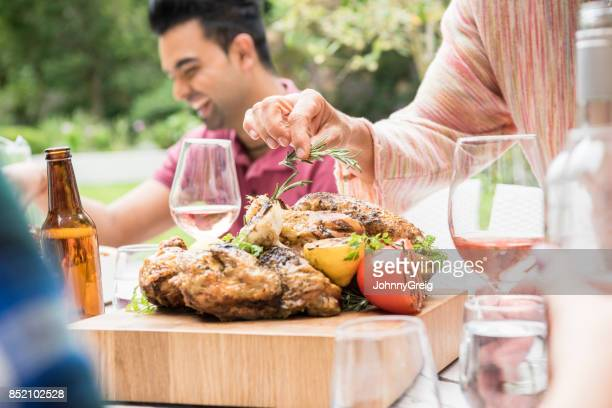 Woman garnishing barbecued chicken on dining table