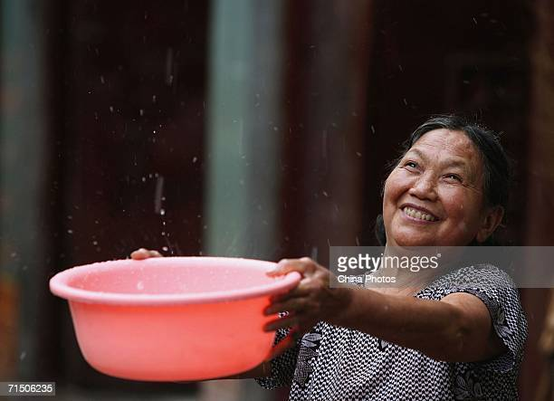 A woman gathers rain from an artificial rainfall launched by the government at Fengming Village of Yunyang County on July 23 2006 in Chongqing...