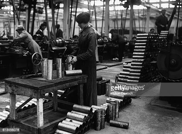 A woman gauges shells in a munitions factory during World War I