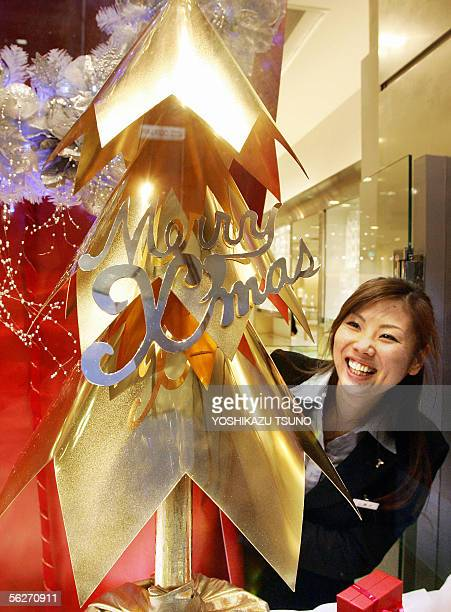 A woman gazes at a pure gold made Christmas tree at Tokyo's jewelery shop Ginza Tanaka 25 November 2005 The Christmas Tree onemeter tall ninekilogram...