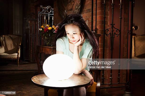 Woman gazes in crystall ball.