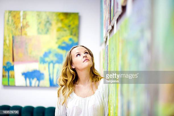 woman gazing at artwork on the wall - konstmuseum bildbanksfoton och bilder