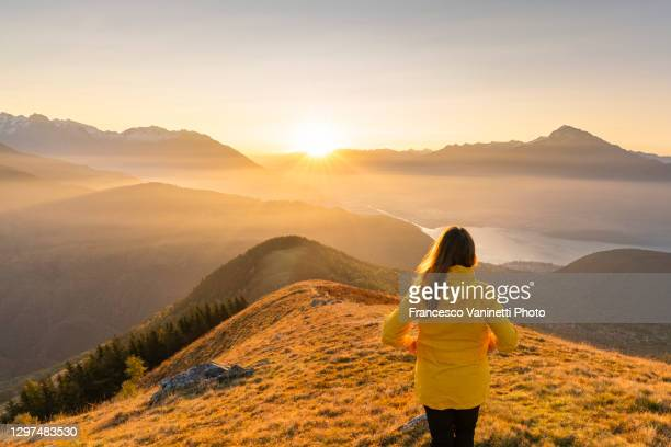 woman gazing at lake como and mountains from high up, italy. - travel foto e immagini stock
