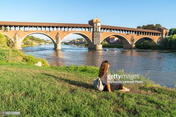 woman gazing at the old bridge and ticino river, pavia, italy. - イタリア パヴィア ストックフォトと画像