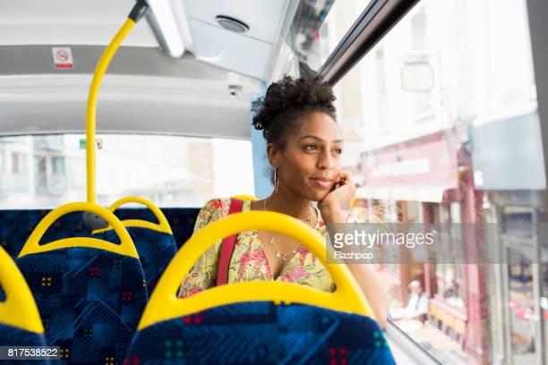 woman gazing out of the window on a bus - transports publics photos et images de collection
