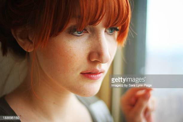 woman gazing out window - ginger lynn stock pictures, royalty-free photos & images