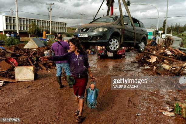 TOPSHOT A woman gestures as a car is removed from the road in the town of Mandra northwest of Athens on November 15 after heavy overnight rainfall in...