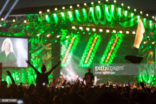 A woman gestures as another is waving a flag during a concert at the 2017 Woodstock Festival Poland on August 4 2017 in Kostrzyn Poland The threeday...