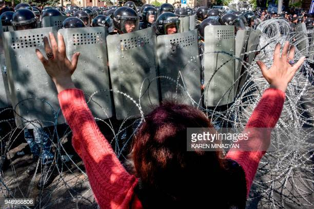 A woman gestures as Armenian special police forces block a street during an opposition rally in central Yerevan on April 16 2018 An opposition leader...